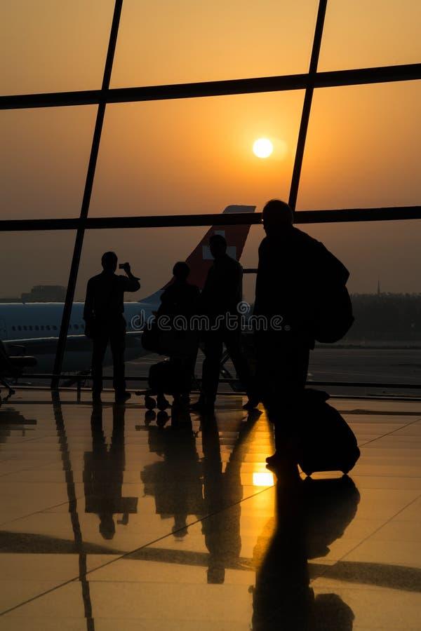 Pequim, China - cerca do setembro de 2015: Silhueta de povos de viagem nos sacos levando do aeroporto fotos de stock royalty free