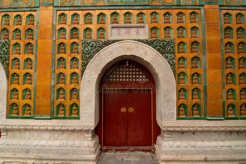 PEQUIM, CHINA - 25 DE DEZEMBRO DE 2017: Porta do templo e mosaico da Buda na parede imagens de stock