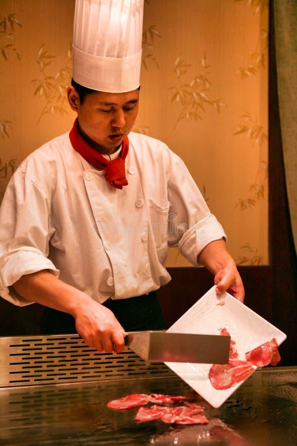 Pequim, China - 9 de junho de 2018: Um cozinheiro chefe chinês está cozinhando o jantar na frente dos visitantes do restaurante fotografia de stock