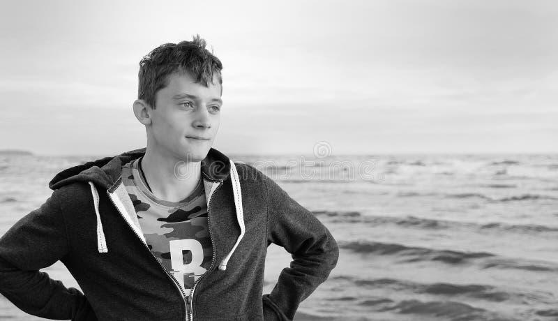 Pequim, foto preto e branco de China Posição feliz livre do homem novo na praia que sente o vento morno olhar na distância, relax fotos de stock