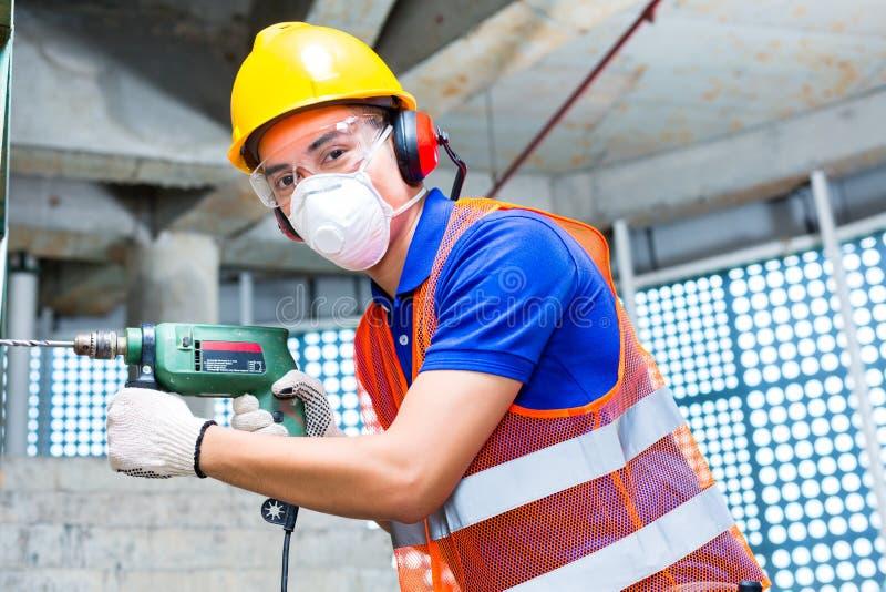 Perçage asiatique de travailleur dans le mur de chantier de construction photographie stock libre de droits