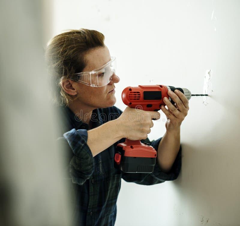 Perçage de femme de construction images stock