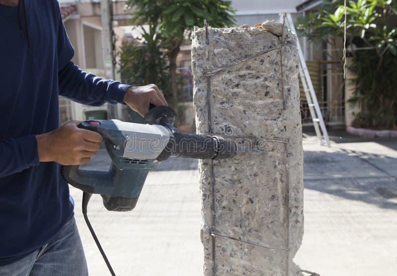 Perçage de main de travailleur sur le poteau concret pour le bâtiment de construction photographie stock