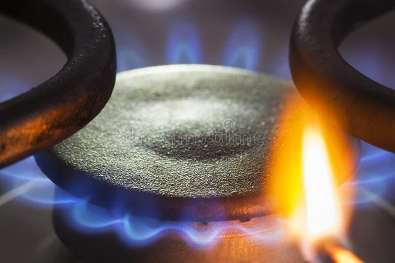 per accendere un bruciatore del gas naturale con una partita fotografia stock