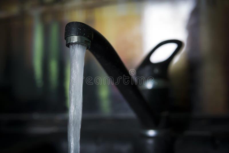 Per acqua potabile dal rubinetto nero nel granito del lavandino nella cucina fotografia stock libera da diritti