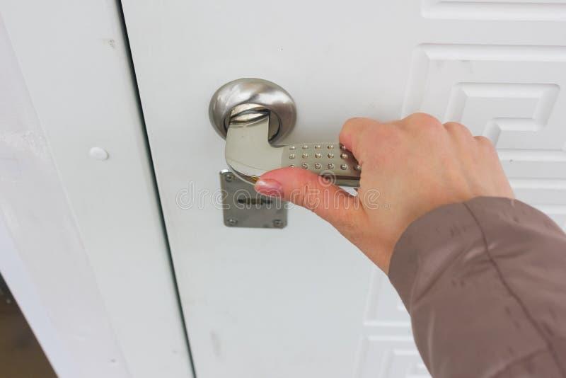 per aprire la porta Tiri la maniglia di porta fotografia stock