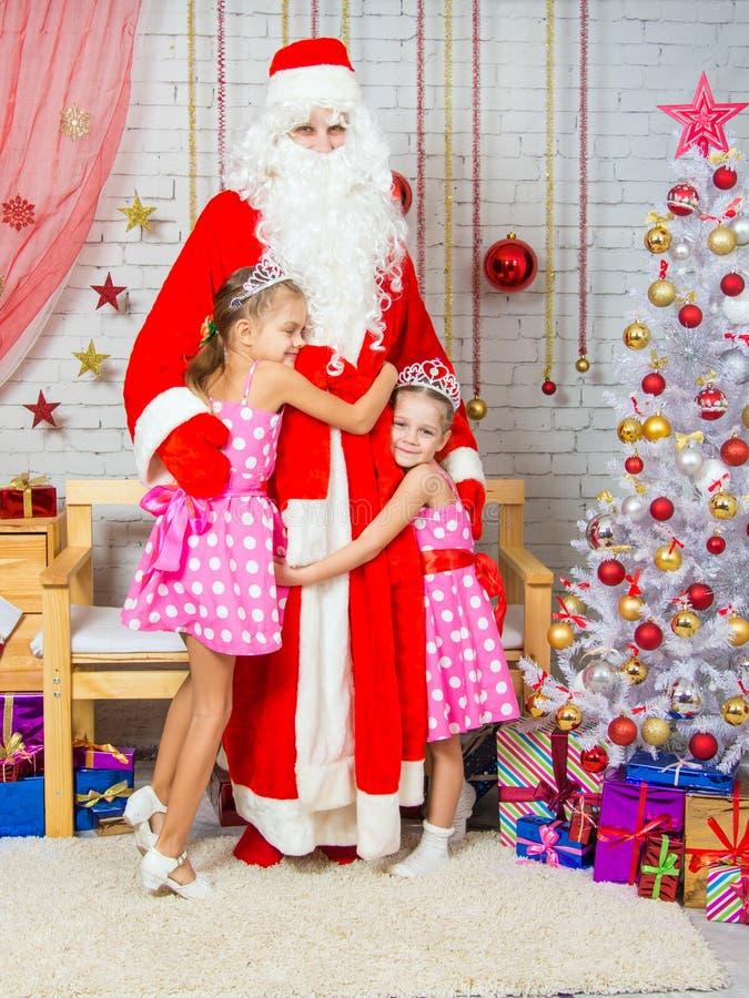 Per i bambini durante il nuovo anno Eve Santa Claus è venuto, essi felicemente lo abbraccia fotografia stock