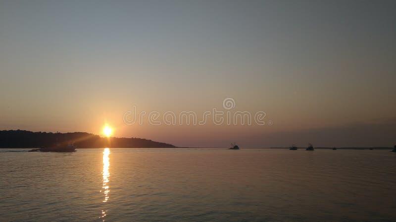 Per la pesca delle navi il giorno inizia con il tramonto fotografia stock
