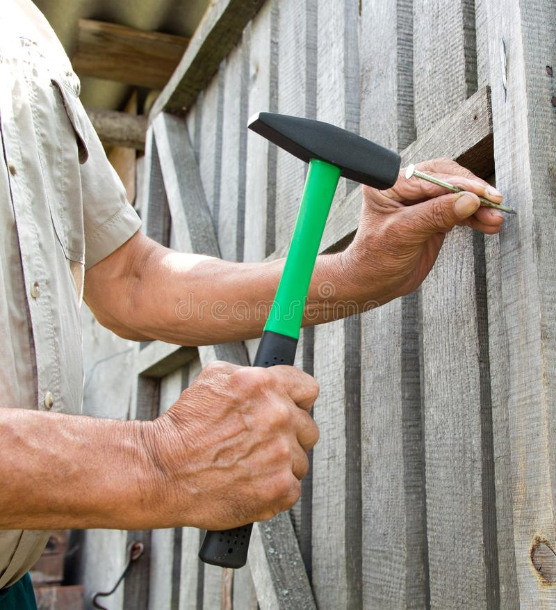 per martellare un chiodo con un martello Carpentiere più anziano del lavoratore immagini stock libere da diritti