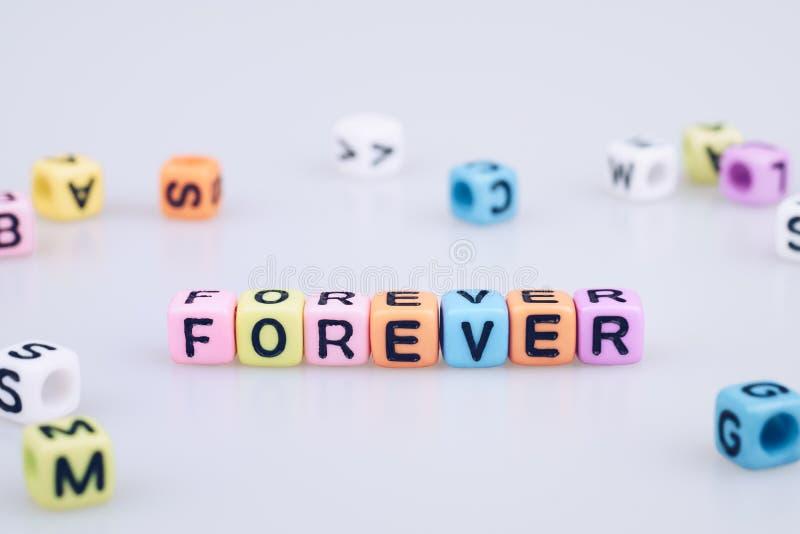 Per sempre esprima il testo scritto sul cubo variopinto con la parola del cubo del bokeh immagine stock libera da diritti
