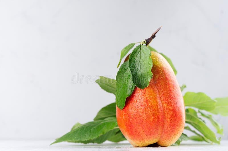 A pera alaranjada madura suculenta com verde novo deixa o close up no interior branco da luz suave Alimento de dieta saudável foto de stock