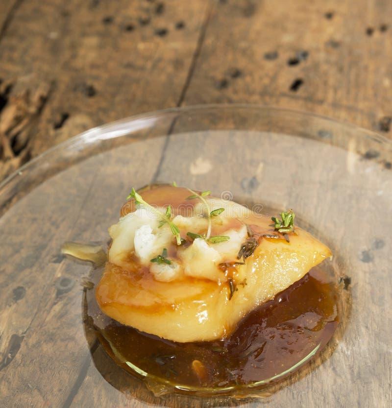 Pera arrostita in caramello con formaggio su vecchio legno fotografia stock