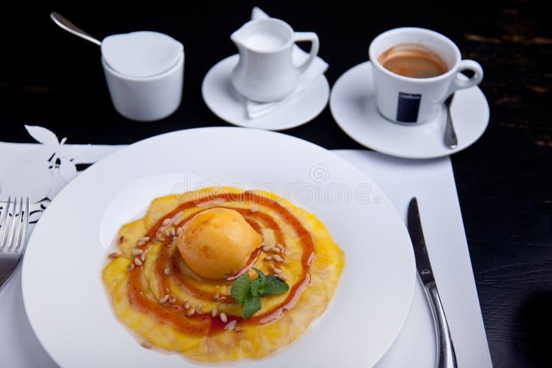 Pera cocida con la bola del helado y la taza del coffe fotografía de archivo libre de regalías
