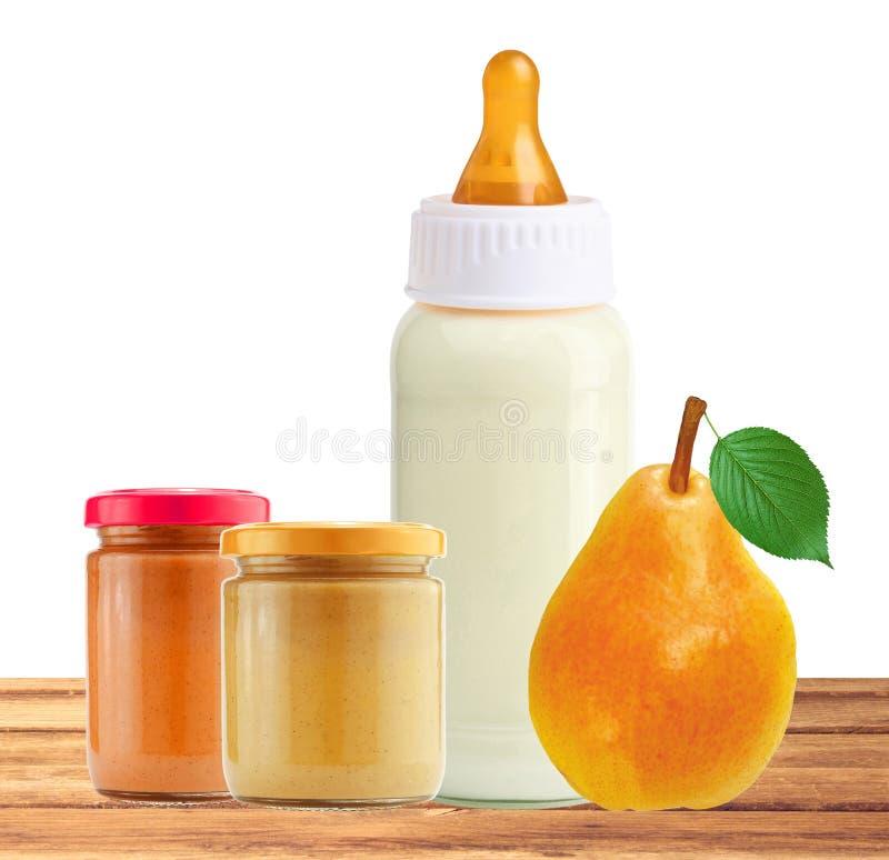Pera, comida para bebê e e garrafa de leite frescos na tabela de madeira imagem de stock royalty free