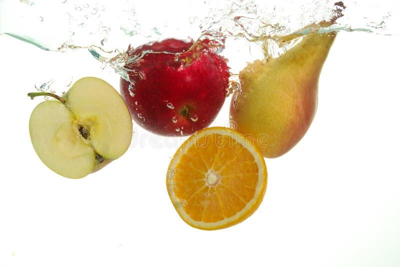 Pera de la manzana de las frutas de Varius y chapoteo anaranjado en agua en blanco imagen de archivo
