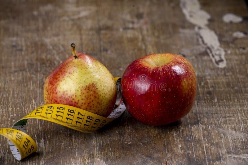 pera e mela che rappresentano i tipi di sovrappesi fotografia stock libera da diritti