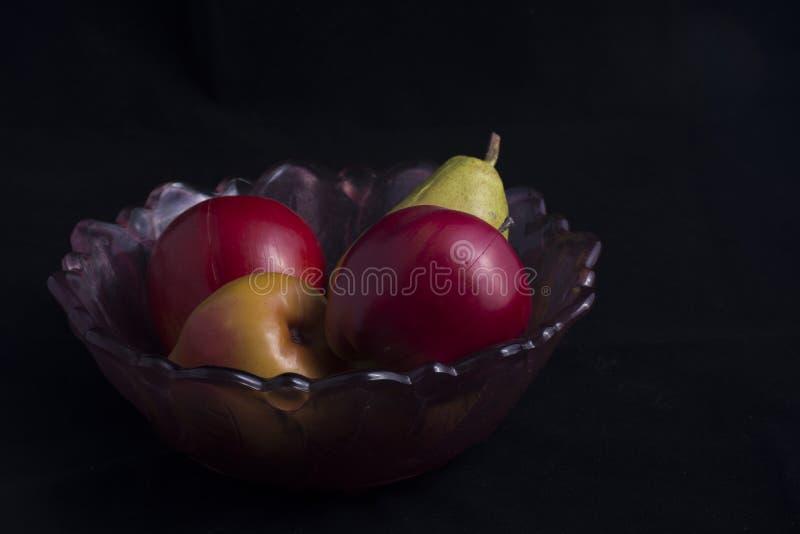 Pera e mela in ciotola antica immagini stock