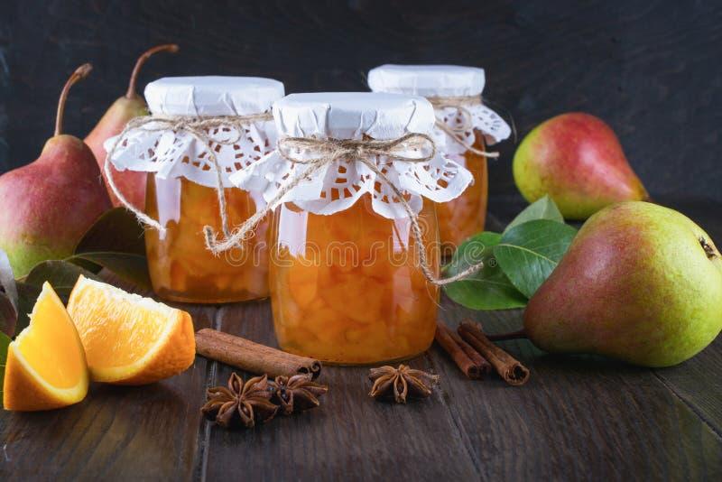 Pera ed inceppamento arancio in barattoli di vetro con le pere, i bastoni di cannella, le stelle dell'anice e le foglie verdi mat fotografie stock