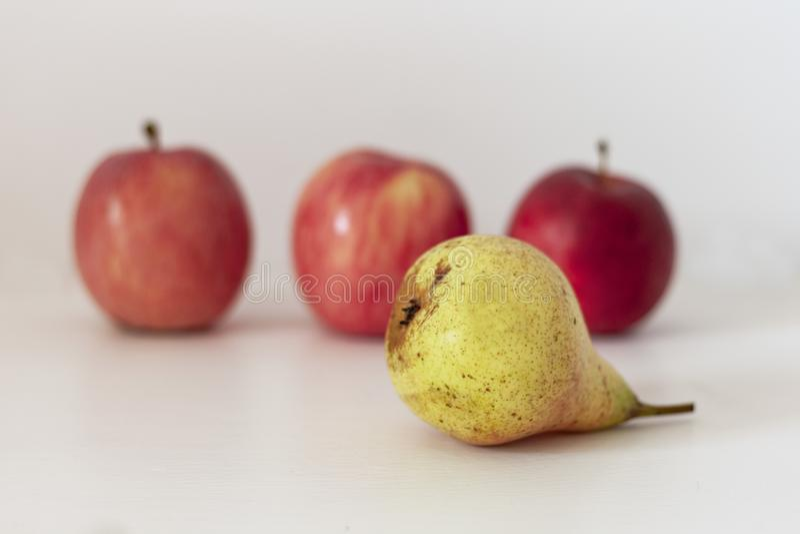 Pera gialla matura e mele rosse su una tavola su un fondo bianco immagini stock