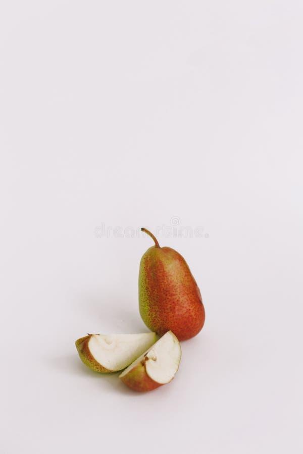 Pera tagliata verde fresca matura dolce con le gocce di acqua, foglie verdi, macchiate sulla tavola di legno bianca fotografia stock libera da diritti
