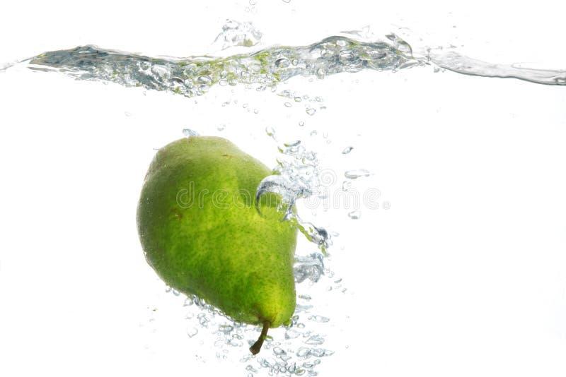 Pera verde en agua foto de archivo