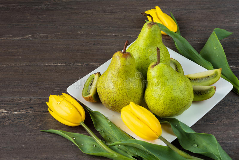 Pera verde, kiwi cortado y tulipanes amarillos en la placa blanca en el tablero de madera gris fotos de archivo