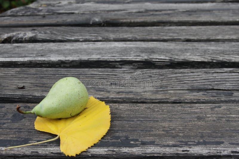 Pera verde su struttura di legno Pera verde organica fresca con la foglia gialla su fondo di legno Modello naturale Sfondo natura immagine stock libera da diritti