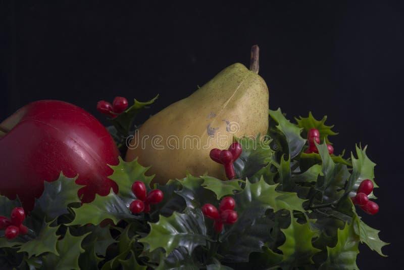 Pera y manzana en acebo foto de archivo