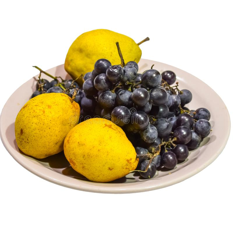 Pera y uvas amarillas en la placa imágenes de archivo libres de regalías