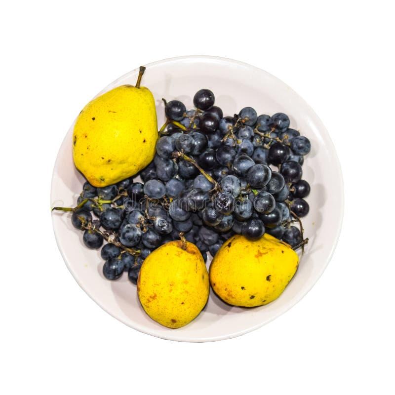 Pera y uvas amarillas en la placa fotografía de archivo libre de regalías