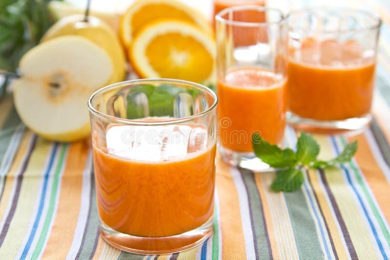 Pera, zanahoria y smoothie anaranjado fotos de archivo