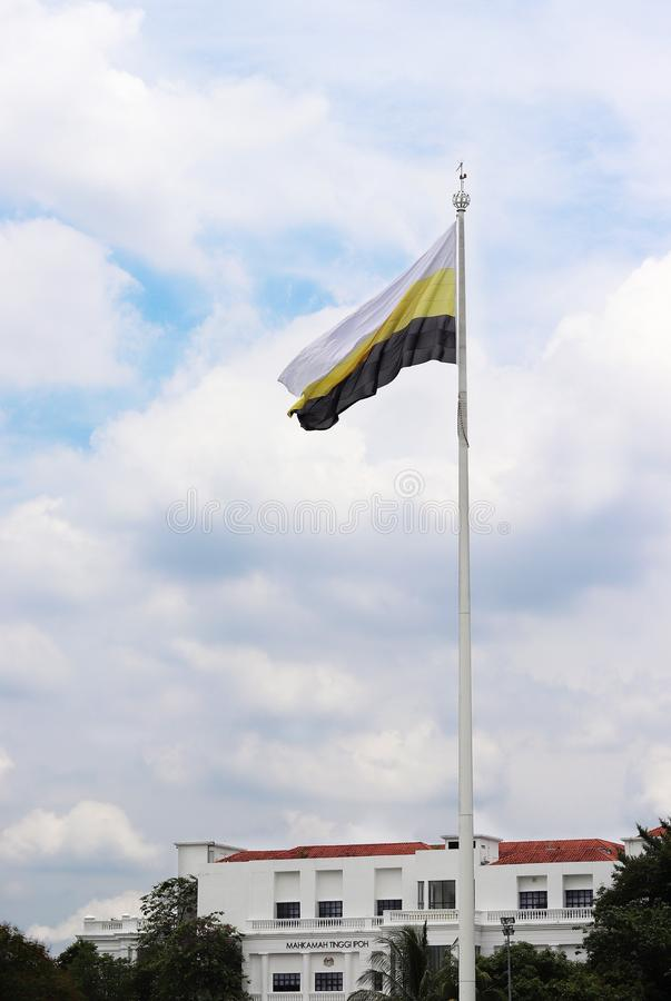 Perak State Flag Mounted At Ipoh Padang. Perak state flag mounted at the giant flagpole at Ipoh Padang, unfurled and flying in the wind under a cloudy sky stock images