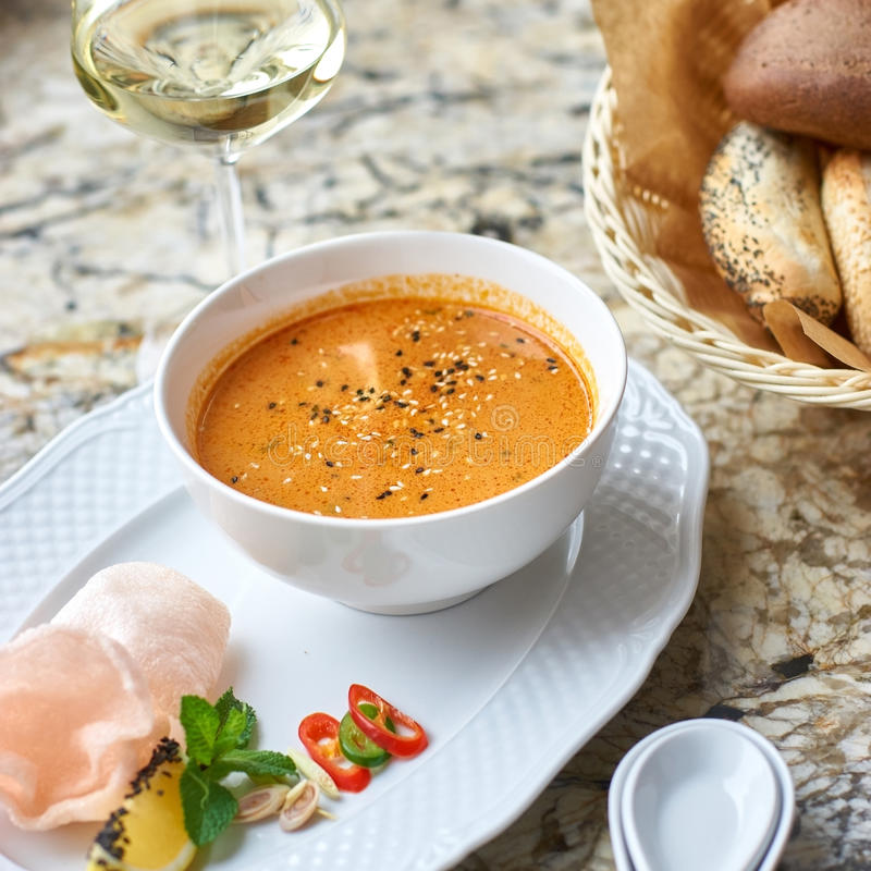 Peranakan cuisine. Singapore Laksa soup. Served with glass of white wine, bread, ceramic spoon, crab chips, slice of lemon and fresh vegetables on marble table stock photography
