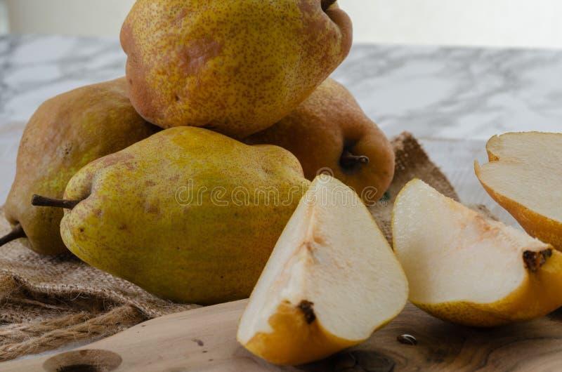 Peras amarillas orgánicas maduras frescas en la tabla de mármol, fotografía de archivo libre de regalías