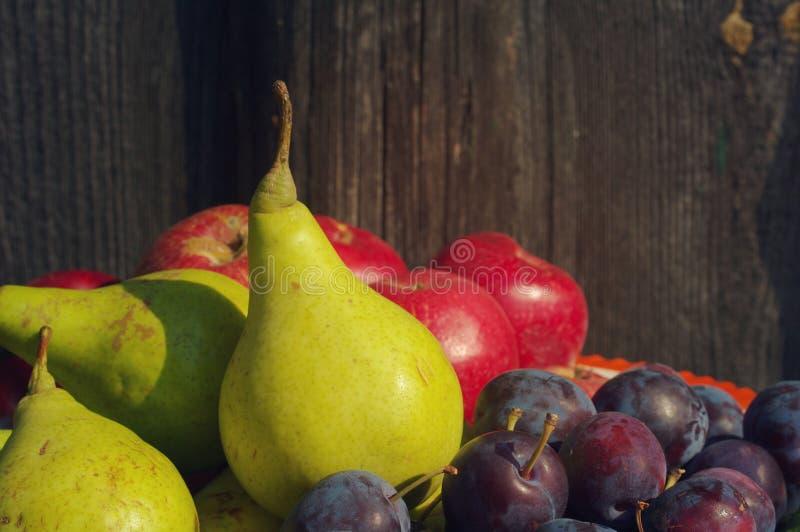 Peras, ameixas e maçãs em um fundo de madeira fotos de stock royalty free