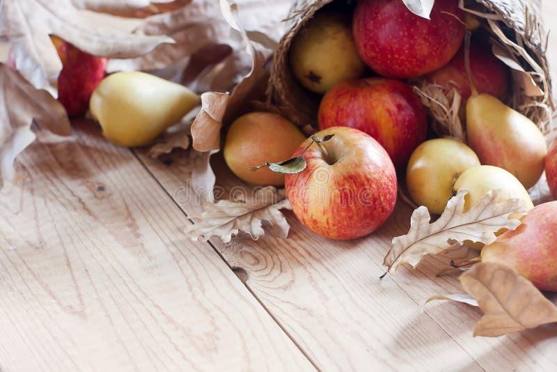 Peras e maçãs com fundo das folhas da queda fotografia de stock royalty free