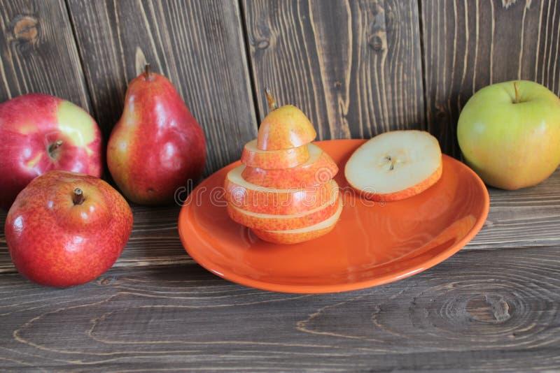 Peras e maçãs vermelhas e verdes em uma tabela de madeira imagem de stock