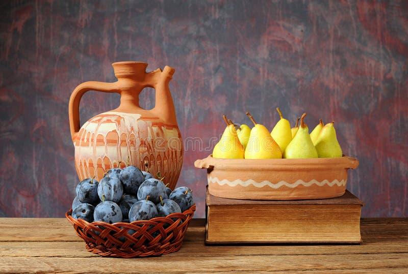 Peras frescas, ciruelos y una garrafa de cerámica imagen de archivo libre de regalías