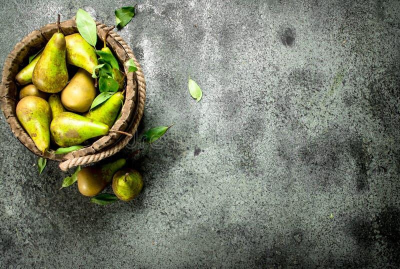 Peras maduras em uma cubeta de madeira fotografia de stock