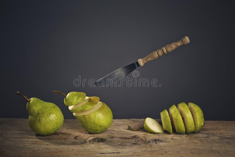 Peras y cuchillo cortados del vuelo imagen de archivo
