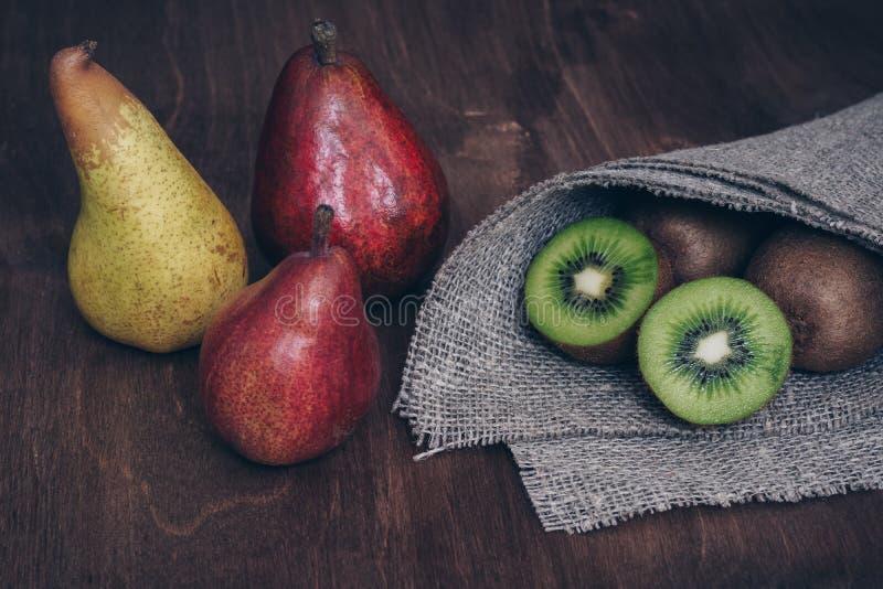 Peras y kiwi en una tabla de madera Aún-vida con la fruta fotos de archivo libres de regalías
