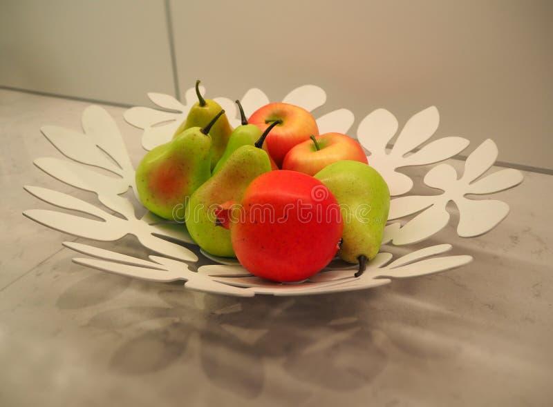 Peras y manzanas en la placa como decoración de la tabla de cocina fotografía de archivo