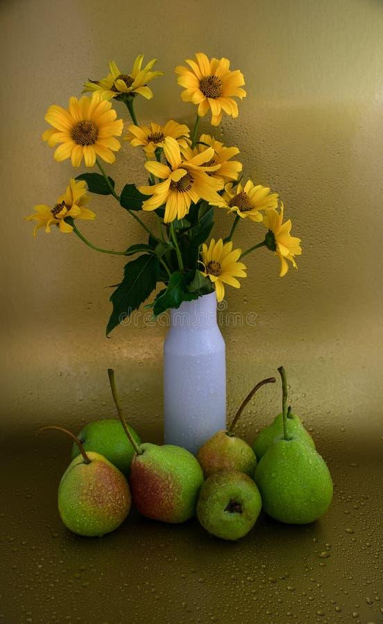Peras y un florero blanco con las flores imágenes de archivo libres de regalías