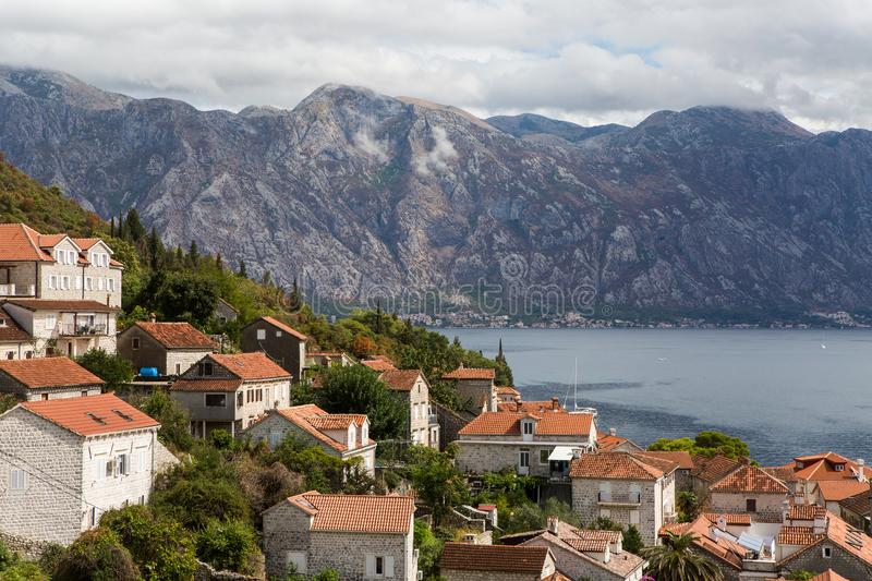 Roofs of old houses in Perast and Bay with mountains in Montenegro stock photo