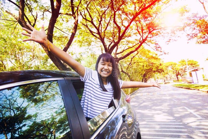 Perca acima da cara da emoção asiática da felicidade do adolescente no carro pessoal contra o ambiente verde da rua urbana da cid fotos de stock