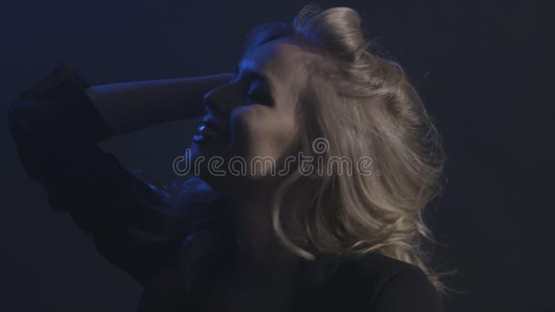Perca acima do retrato da cara bonita da mulher com o cabelo surpreendente louro longo encaracolado isolado no fundo preto a??o foto de stock royalty free