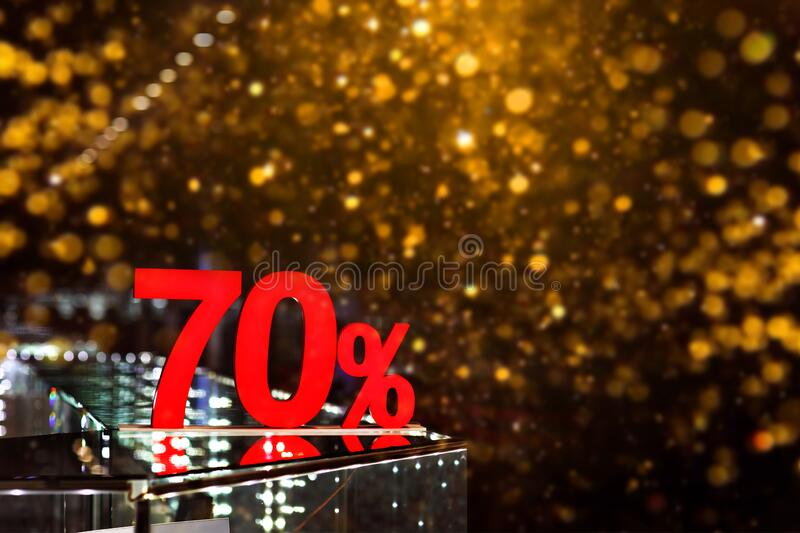70 percent discount with golden bokeh background. Discounts in the shopping center. Seasonal sale, black friday. Red label stock photography