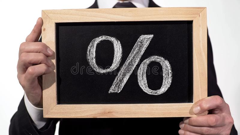 Percent sign drawn on blackboard in businessman hands, deposit interest rate royalty free stock photo
