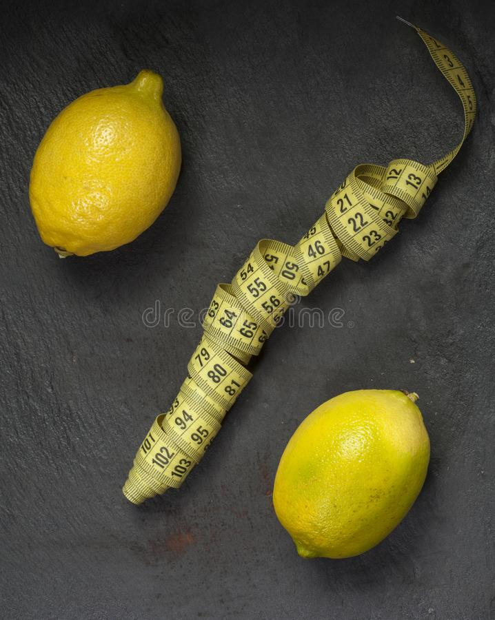 The percent sign in the form of two lemons and a centimeter to measure the waist. royalty free stock photo