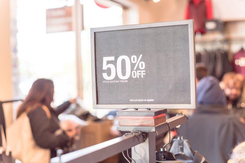 50 percenten van verkoopteken over kleren bij warenhuis met klant het winkelen stock foto's